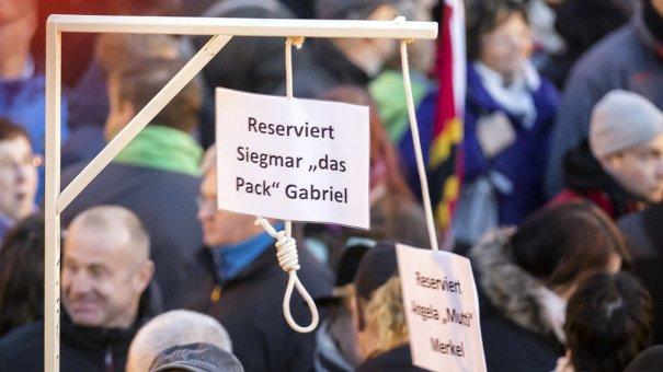 Sjarmerende! Galge reservert til pakket Sigmar Gabriel (I bakgrunnen kan man skimte det som ofte ser ut som et norsk flagg på kveldsbilder. Det er det ikke, det er et gammelt forslag til det tyske flagget, med kors.) Foto: Nadine Lindner/DPA